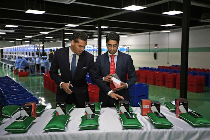 Sahir Berry, CEO of AfriOne, and Hemang Kapur, a director of AfriOne, prepare a display of AfriOne Gravity Z1 smartphones during a launch event in April 2017. (Photo: George Osodi/Bloomberg via Getty Images)