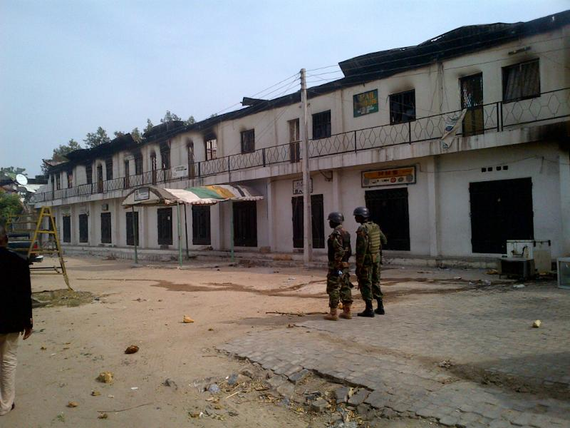 In this photo taken with a mobile phone, soldiers stand outside a burnt out shopping mall in Maiduguri, Nigeria, Monday, Oct. 8, 2012. Nigerian soldiers angry about the killing of an officer razed buildings and shot dead more than 30 civilians Monday in a northeastern city long under siege by a radical Islamist sect. An Associated Press reporter in Maiduguri, the spiritual home of the sect known as Boko Haram, counted the dead while on a tour of the still-smoldering neighborhood.  (AP Photo / Abdulkareem Haruna)