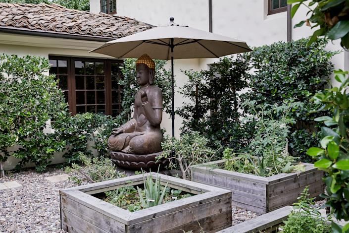 "<div class=""caption""> One of the outdoor patios has an imported Thai Buddha statue and raised beds filled with vegetables. </div>"