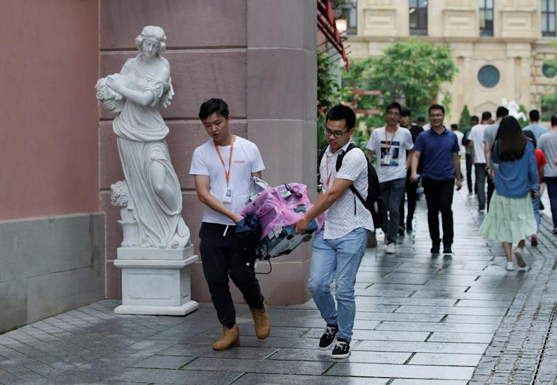 Employees carry an equipment past a sculpture at Huawei Songshan Lake New Campus in Dongguan, Guangdong province, China May 29, 2019. Picture taken May 29, 2019. REUTERS/Jason Lee