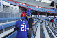 Buffalo Bills fans Scott Hammond, right, and his son Landon pose for a photograph as their team warms up before an NFL wild-card playoff football game against the Indianapolis Colts Saturday, Jan. 9, 2021, in Orchard Park, N.Y. The Hammonds were among the lucky 6,700 few to land tickets for the Bills wild-card playoff against the Colts for Buffalo's first home playoff game in 24 years. (AP Photo/Jeffrey T. Barnes)