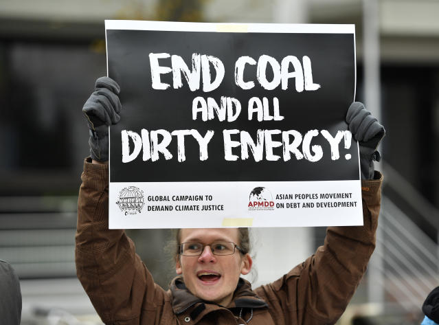 In this Wednesday, Nov. 15, 2017, file photo, protestor holds a sign demanding to end coal burning during the 23rd Conference of the Parties (COP) climate talks in Bonn, Germany. (AP Photo/Martin Meissner)