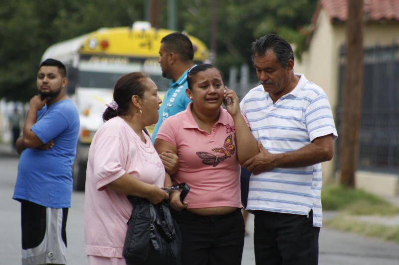 """In this Aug. 28, 2013 photo, an unidentified relative is escorted from the scene where a bus driver was allegedly killed by a self-styled """"bus driver hunter,"""" in Ciudad Juarez, Mexico. Mexican prosecutors said Monday, Sept. 2, 2013, they are investigating claims that a woman who killed two bus drivers last week in this northern border city was seeking revenge for alleged sexual abuse of female passengers. (AP Photo/Raymundo Ruiz)"""