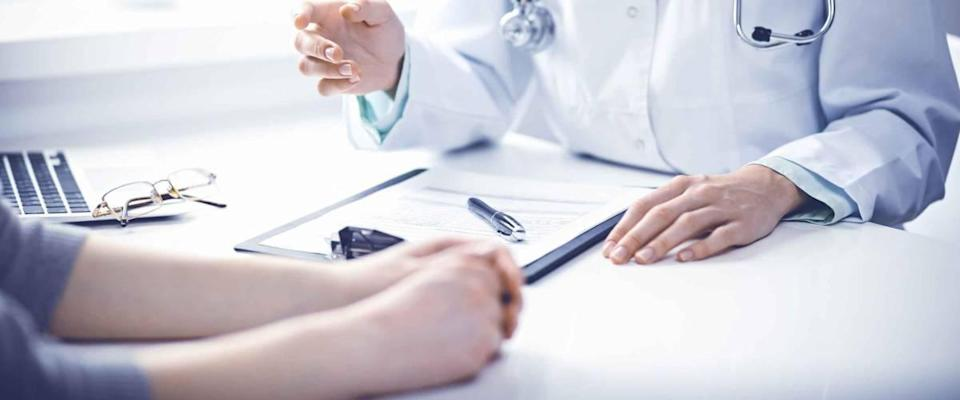 Close up of doctor going over forms with patient across the table from them.