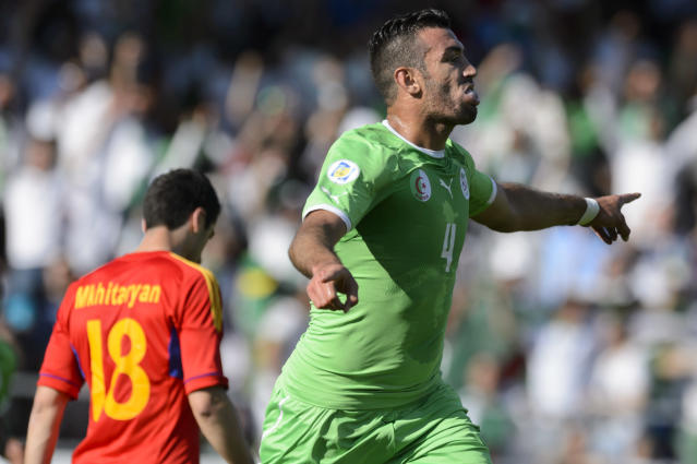 Algeria defender Essaid Belkalem, right, celebrates the first goal in front of Armenian midfielder Henrikh Mkhitaryan, during an international friendly test match ahead of the FIFA World Cup 2014 in Brazil, between the national soccer teams of Algeria and Armenia at the Stade de Tourbillon in Sion, Switzerland, Saturday, May 31, 2014. (AP Photo/Keystone,Laurent Gillieron)