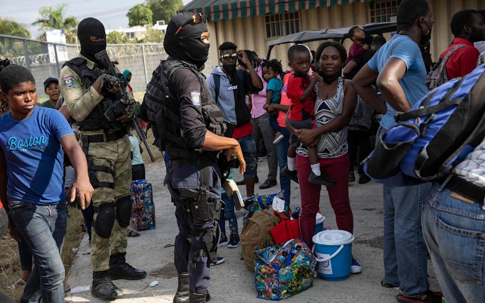 Haitian migrants deported from the US gather after arriving to the Toussaint Louverture International Airport in Port-au-Prince - AP