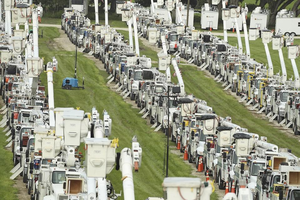 About 250 electrical utility trucks are lined up at Duke Energy's staging location in The Villages of Sumter County on Tuesday, July 6, 2021. Elsa may hit central Florida on Tuesday and Wednesday, with possible localized flooding. Duke Energy staged a total of about 500 trucks at the location, and they will be deployed following Elsa to repair damage to electrical lines and poles. (Stephen M. Dowell/Orlando Sentinel via AP)