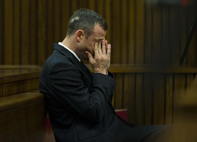 Oscar Pistorius rubs his face as he listens to forensic evidence being given in court in Pretoria, South Africa, Thursday, April 17, 2014. Pistorius is charged with the murder of his girlfriend, Reeva Steenkamp, on Valentines Day in 2013. (AP Photo/Alet Pretorius, Pool)