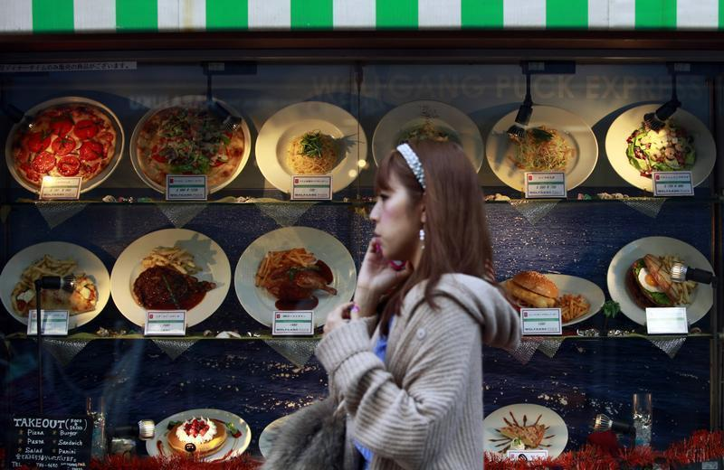 Woman passes a restaurant in Tokyo's Harajuku shopping district
