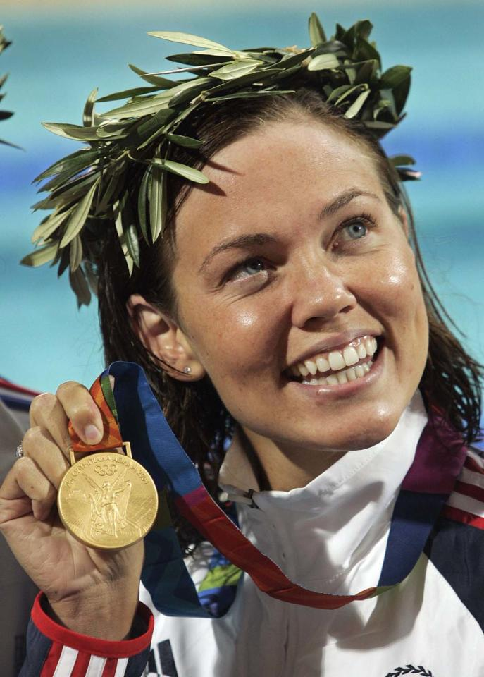 Gold medalist Natalie Coughlin of the U.S. shows her medal after winning the 100m backstroke the 2004 Olympic Games Monday, August 16 2004 in Athens, Greece. (AP Photo/Mark J. Terrill)