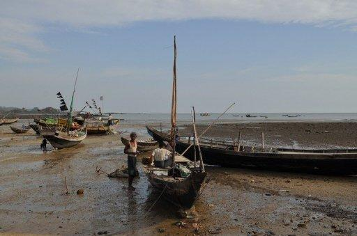 Fishermen standing by their boats on the island of Shweri Chai, off the western city of Sittwe, in April