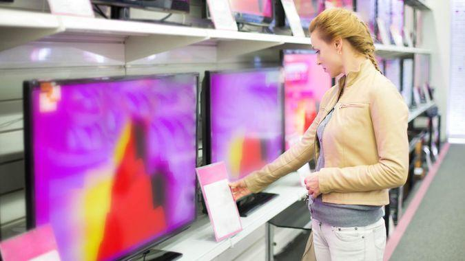 The woman buys a TV in shop.