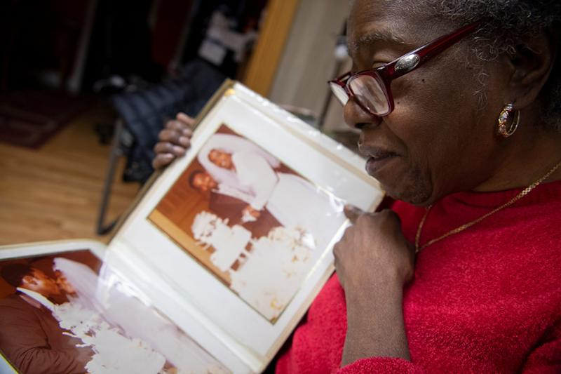 Patricia Blair is overcome with emotion as she looks through her wedding photo album in the living room of her Philadelphia home that she is leaving after a reverse mortgage foreclosure.