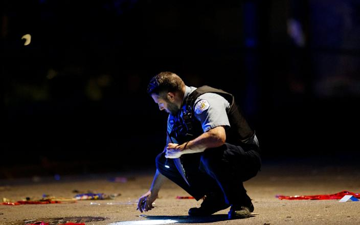An officer investigates the scene of a shooting in Chicago over the Fourth of July weekend - Armando L. Sanchez/Chicago Tribune