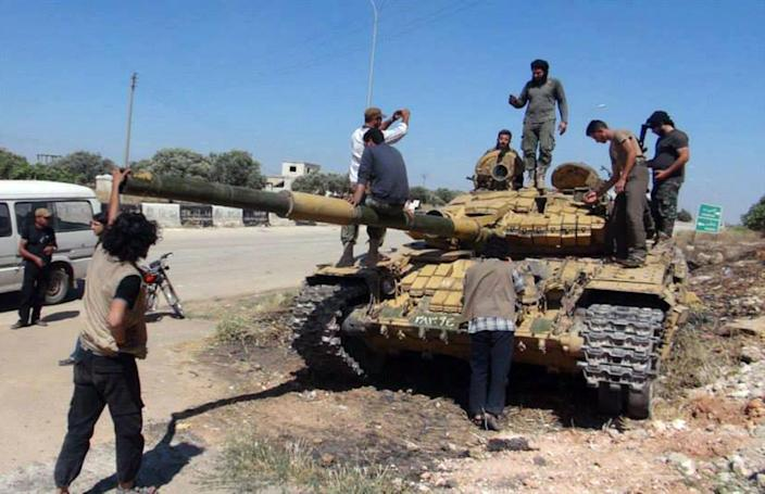 In this Friday, June 14, 2013 citizen journalism image provided by Edlib News Network, ENN, Syrian rebels stand on top of a tank they took after storming the Iskan military base in Idlib province, northern Syria. After weeks of fighting the rebels captured tanks as well as other vehicles and artillery in the area. (AP Photo/Edlib News Network ENN) THE ASSOCIATED PRESS IS UNABLE TO INDEPENDENTLY VERIFY THE AUTHENTICITY, CONTENT, LOCATION OR DATE OF THIS HANDOUT PHOTO.