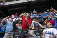 Fans scramble for a foul ball during the first inning of a baseball game between the Texas Rangers and the Toronto Blue Jays, Monday, April 5, 2021, in Arlington, Texas. (AP Photo/Jeffrey McWhorter)