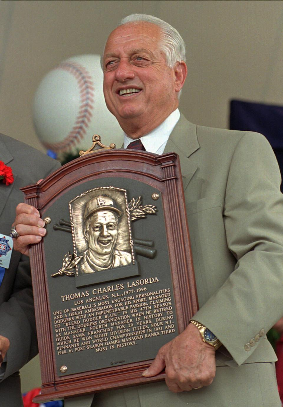 Tommy Lasorda poses with his Hall of Fame plaque after his induction Sunday, Aug. 3, 1997 in Cooperstown, N.Y. (AP Photo/ Dave Jennings)