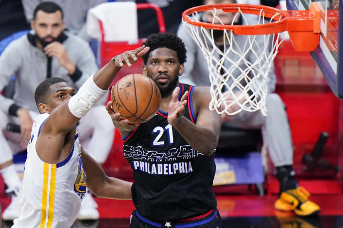 Philadelphia 76ers' Joel Embiid, right, goes up for a shot against Golden State Warriors' Kevon Looney during the second half of an NBA basketball game, Monday, April 19, 2021, in Philadelphia. (AP Photo/Matt Slocum)
