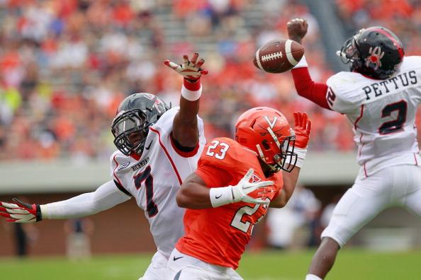 Running back Khalek Shepherd #23 of the Virginia Cavaliers, defensive back DeShawn Holmes #7 of the Richmond Spiders, and defensive back Wayne Pettus #2 of the Spiders reach for the ball at Scott Stadium on September 1, 2012 in Charlottesville, Virginia. (Photo by Geoff Burke/Getty Images)