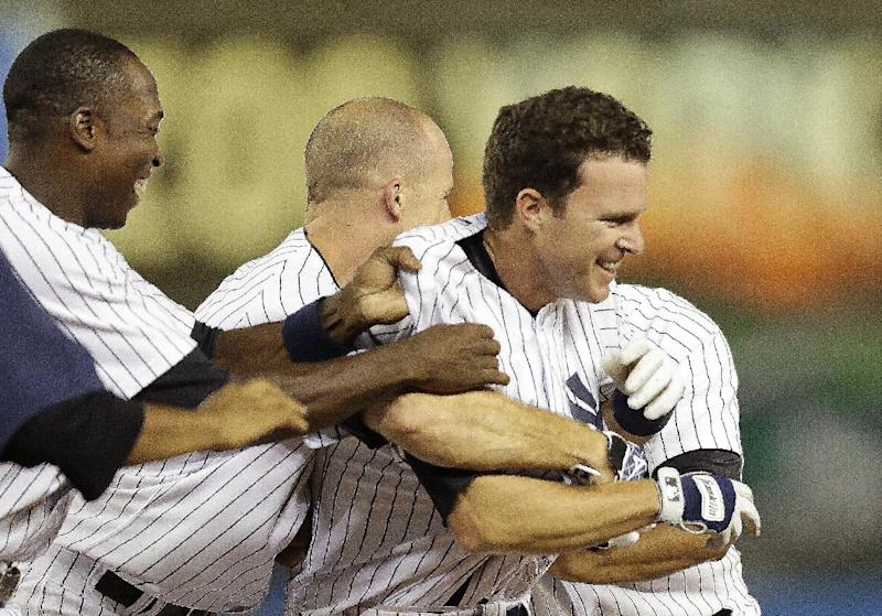 New York Yankees Alfonso Soriano, left, and Brett Gardner celebrate with Jayson Nix, right, after he hit the game-winning RBI single to lift the Yankees to a 3-2 win over the Toronto Blue Jays in the second baseball game of a doubleheader at Yankee Stadium, Tuesday, Aug. 20, 2013, in New York. (AP Photo/Kathy Willens)