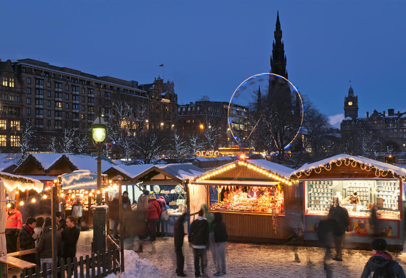 Edinburgh, Scotland - 1st December 2010: Shoppers visiting traditional wooden stalls at a public Christmas market situated next to Princes Street in the city centre of Edinburgh, with Jenners department store, the Scott Monument and the Balmoral Hotel visible on the skyline.