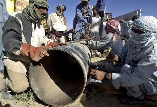 Pakistani employees of natural gas repair a damaged pipeline
