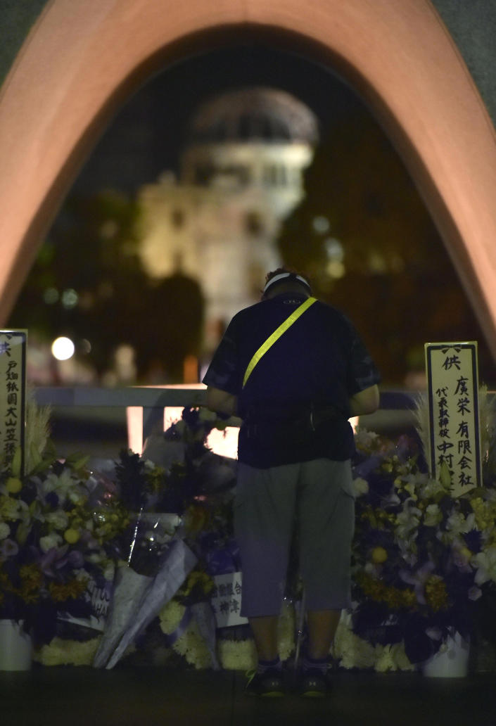 A man prays in front of the cenotaph dedicated to the victims of atomic bombing at Hiroshima Peace Memorial Park in Hiroshima, western Japan, Monday, Aug. 6, 2018, marking the 73rd anniversary of the bombing. Atomic Bomb Dome is seen in the background. (Shingo Nishizume/Kyodo News via AP)