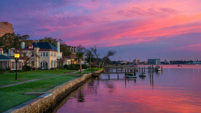 Houses and Riverfront of the Elizabeth River in Portsmouth, Virginia during dawn with magenta, purple, and pink clouds.
