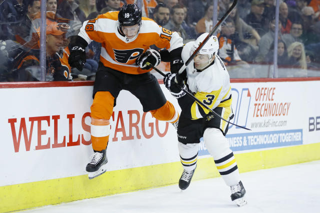 Philadelphia Flyers' Tyler Pitlick, left, tries to jump past Pittsburgh Penguins' Jack Johnson during the second period of an NHL hockey game, Tuesday, Jan. 21, 2020, in Philadelphia. (AP Photo/Matt Slocum)