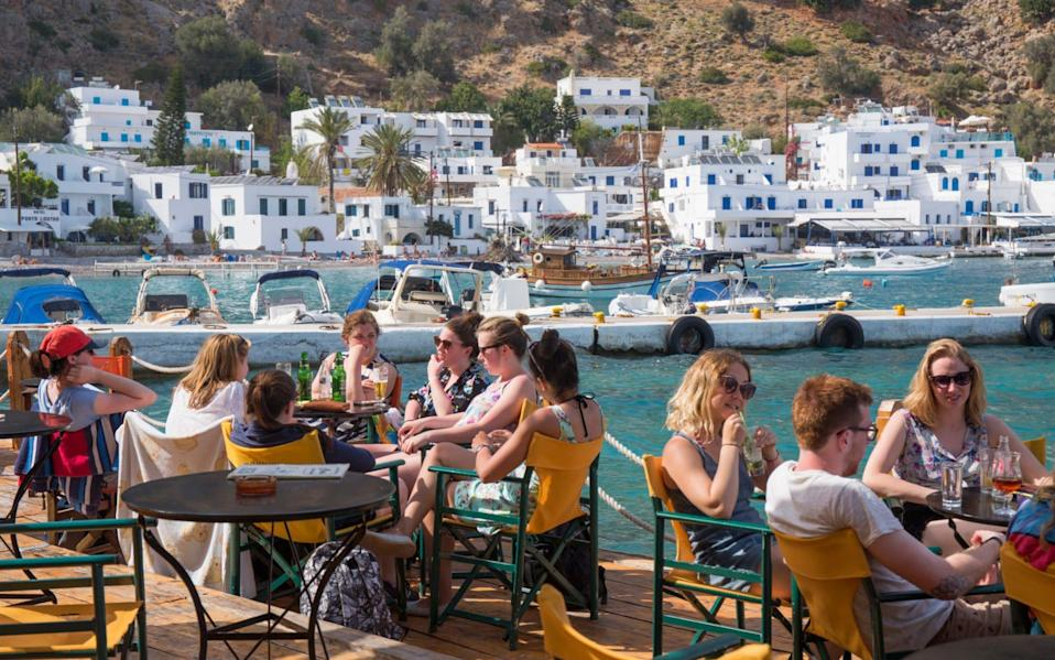 Guests dining at a waterfront restaurant in Loutro, Crete - Getty