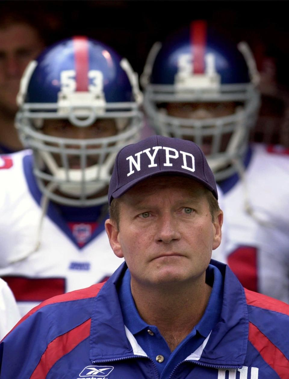 FILE - In this Sept. 23, 2001, file photo, New York Giants coach Jim Fassel wears a New York Police Department cap while pausing during a moment of silence before an NFL football game against the Kansas City Chiefs at Arrowhead Stadium in Kansas City, Mo. A backup quarterback and holder for the Giants in 2001, New York Giants offensive coordinator Jason Garrett spoke Thursday, Sept. 9, 2021, about the Sept. 11 attacks and the tragedy that claimed almost 3,000 lives that day. (AP Photo/Charlie Riedel, File)