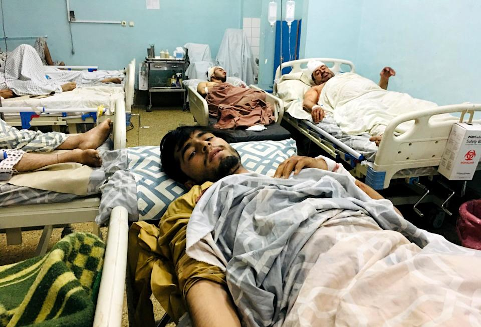 Wounded Afghans lie on a bed at a hospital after the deadly explosions (AP)