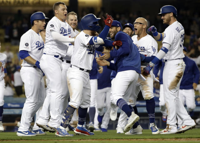 Los Angeles Dodgers' Alex Verdugo, third from left with helmet, is mobbed by teammates after driving in the game-winning run with a sacrifice fly ball during the ninth inning of a baseball game against the New York Mets Wednesday, May 29, 2019, in Los Angeles. (AP Photo/Marcio Jose Sanchez)