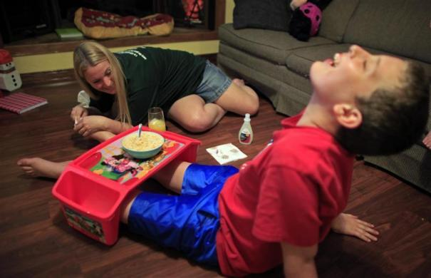 Parker Roos, who suffers from Fragile X, laughs as his mother Holly removes toenail polish from his feet at their home in Canton, Illinois, April 3, 2012.