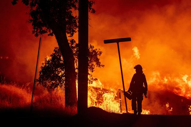 <p>A firefighter lights backfires during the Carr fire in Redding, Calif. on July 27, 2018. (Photo: Josh Edelson/AFP/Getty Images) </p>