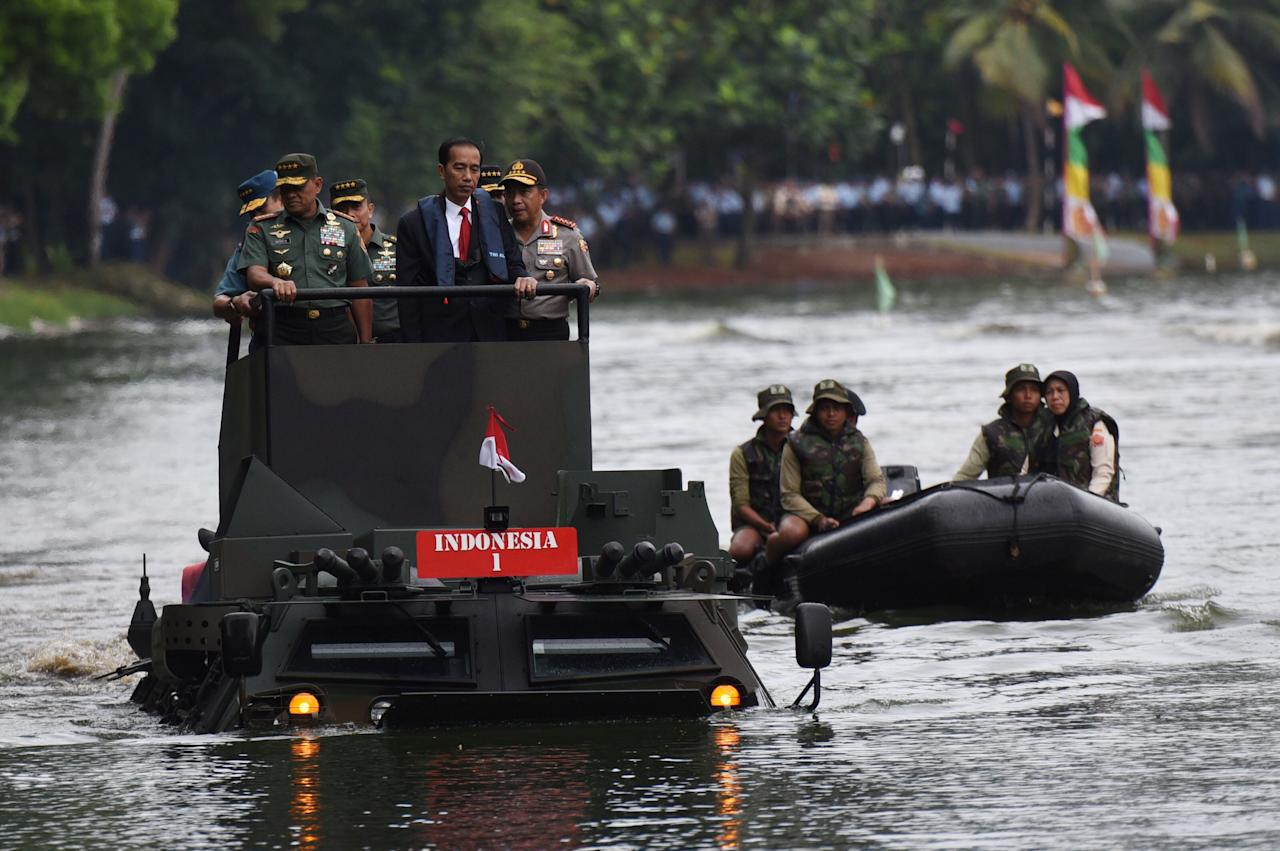(L-R) Indonesia Military Chief Gatot Nurmantyo, Indonesia President Joko Widodo, and Indonesia Police Chief Tito Karnavian stand on a military amphibious vehicle Anoa 2 while crossing a lake at a military headquarters in Jakarta, Indonesia, January 16, 2017,  in this photo taken by Antara Foto. Antara Foto/Akbar Nugroho Gumay/via REUTERS ATTENTION EDITORS - THIS IMAGE WAS PROVIDED BY A THIRD PARTY. FOR EDITORIAL USE ONLY. MANDATORY CREDIT. INDONESIA OUT. TPX IMAGES OF THE DAY
