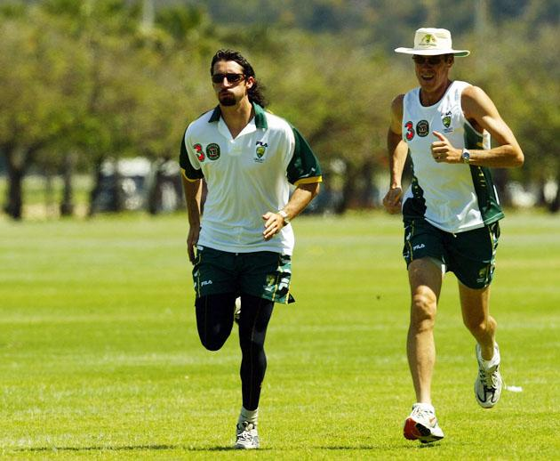Jason Gillespie of Australia runs with coach John Buchanan during a training session outside the Hyatt Hotel on October 3, 2003 in Perth, Australia. (Photo by Hamish Blair/Getty Images)