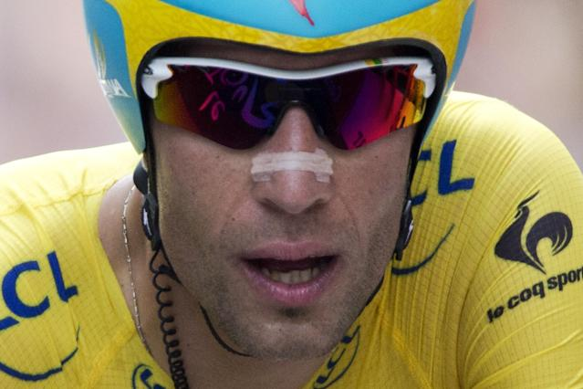Italy's Vincenzo Nibali, wearing the overall leader's yellow jersey, crosses the finish line of the twentieth stage of the Tour de France cycling race, an individual time-trial over 54 kilometers (33.6 miles) with start in Bergerac and finish in Perigueux, France, Saturday, July 26, 2014. (AP Photo/Peter Dejong)