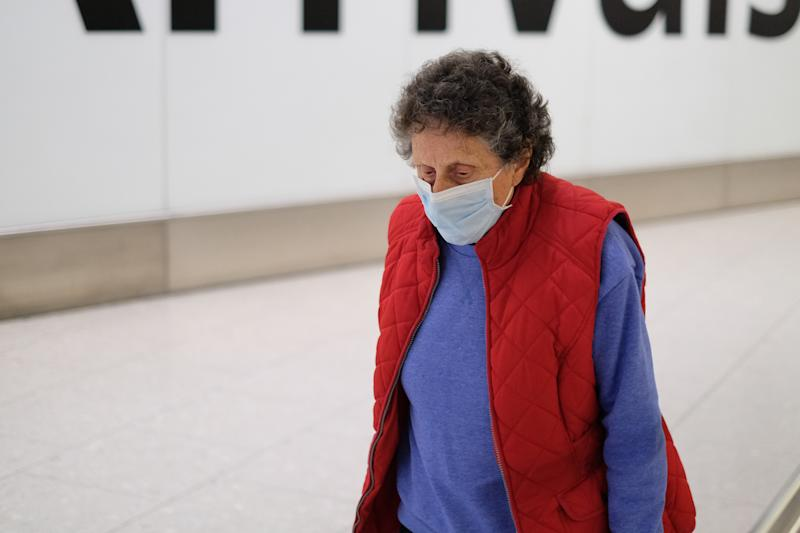 Passengers arriving at Heathrow Airport wear face masks as four patients are tested for coronavirus in Scotland (SWNS)