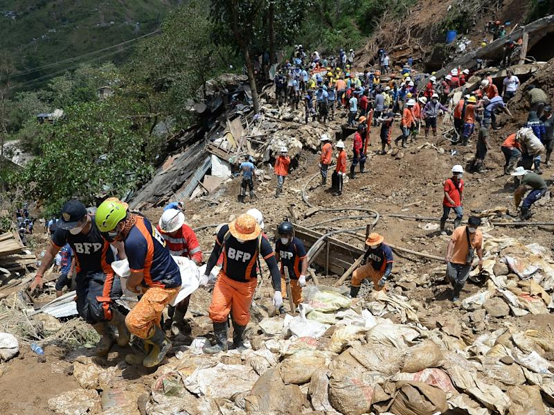 Rescuers carry a body bag containing the body of a victim of a landslide during heavy rains at the height of Typhoon Mangkhut in Itogon town (AFP Photo/TED ALJIBE)