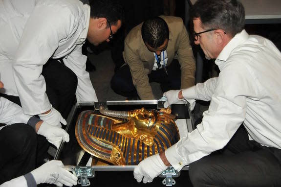 Officials transport the restored mask.