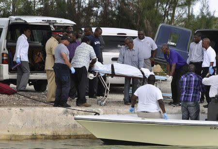 Rescue workers carry from a boat to a hearse the body of one of the victims of a small plane that crashed in East Grand Bahama