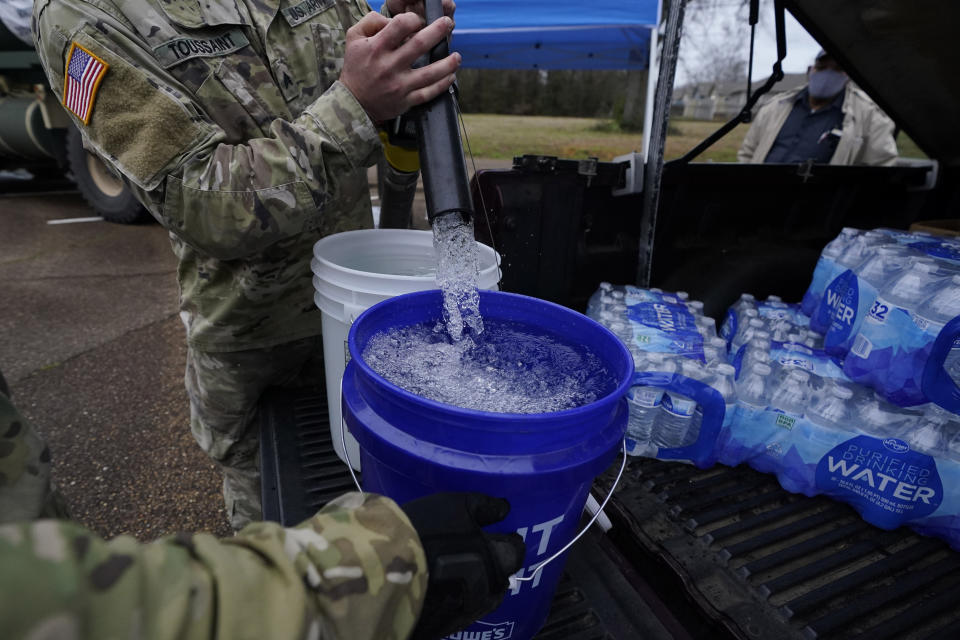 Mississippi Army National Guard Sgt. Chase Toussaint with the Maneuver Area Training Equipment Site of Camp Shelby, right, fills 5-gallon buckets with non-potable water, Monday, March 1, 2021, at a Jackson, Miss., water distribution site on the New Mt. Zion Missionary Baptist Church parking lot. Water for flushing toilets was being distributed at seven sites in Mississippi's capital city — more than 10 days after winter storms wreaked havoc on the city's water system because the system is still struggling to maintain consistent water pressure, authorities said. (AP Photo/Rogelio V. Solis)