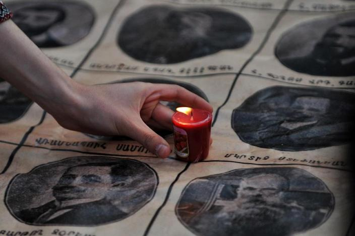 A woman places a lit candle on portraits of Armenian intellectuals who were deported under Ottoman rule during a 2014 ceremony in Istanbul (AFP Photo/Ozan Kose)