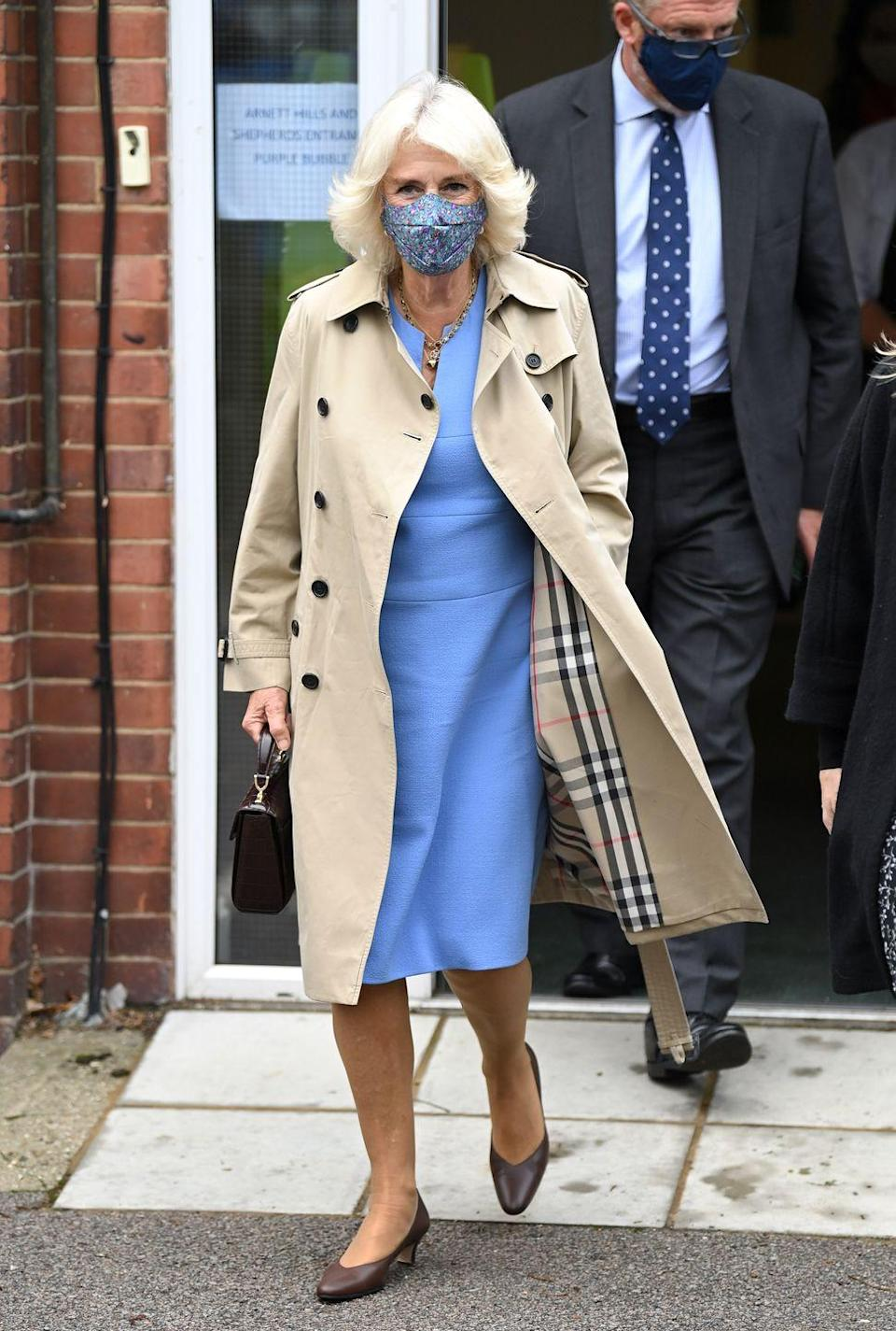 """<p>Few garments are quite as characteristically British as <a href=""""https://www.townandcountrymag.com/style/fashion-trends/g34360257/meghan-markle-kate-middleton-royal-trench-outfit-photos/"""" rel=""""nofollow noopener"""" target=""""_blank"""" data-ylk=""""slk:the classic Burberry trench"""" class=""""link rapid-noclick-resp"""">the classic Burberry trench</a>. Camilla embraced this preppy look by pairing it with a powder blue dress and matching mask. </p>"""