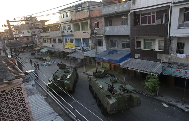"""Navy armored vehicles are seen during an operation to occupy the Mare slum complex in Rio de Janeiro, Brazil, Sunday, March 30, 2014. The Mare complex of slums, home to about 130,000 people and located near the international airport, is the latest area targeted for the government's """"pacification"""" program, which sees officers move in, push out drug gangs and set up permanent police posts. (AP Photo/Silvia Izquierdo)"""