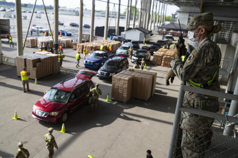 A Indiana National Guardsmen watches over the distribution of food at the Indianapolis Motor Speedway in Indianapolis, Saturday, May 23, 2020. Gleaners Food Bank of Indiana expected to distribute boxes of fresh produce, lean meat, and dairy to more than 5,000 people at the event. The Speedway hosted the event on what would have been the eve of the Indianapolis 500 that was postponed due to the coronavirus outbreak. (AP Photo/Michael Conroy)