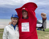 """Gavin Kidd, right, and his wife, Lesley Kidd, left, cheer for Europe during a Ryder Cup golf practice at Whistling Straits outside Sheboygan, Wis., Thursday, Sept. 23, 2021. The Kidds live in Houston, but Gavin is originally from Liverpool, England, and Lesley is from Scotland. Gavin is wearing a mailbox costume to honor European golfer Ian Poulter, who has been nicknamed """"The Postman"""" because he delivers so consistently in Ryder Cup competition. (AP Photo/Steve Megargee)"""