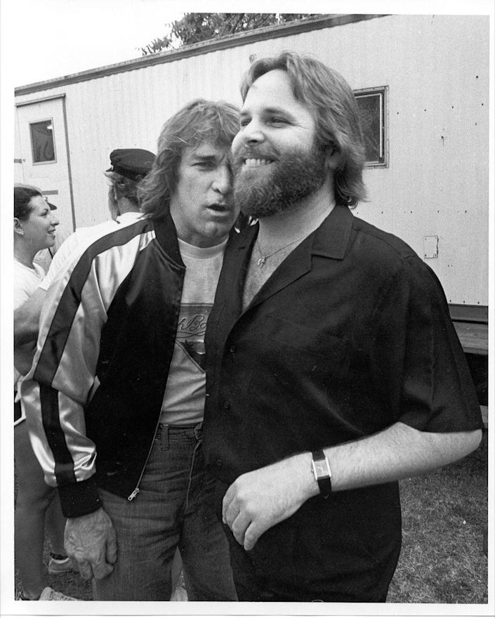 <p>Dennis Wilson and Carl Wilson of The Beach Boys hang out after an outdoor concert in 1975. </p>