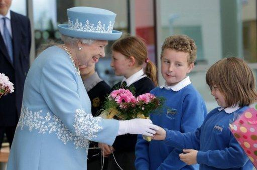 Britain's Queen Elizabeth II is given flowers during a visit to the South West Acute Hospital in Enniskillen, Northern Ireland, on June 26. The British monarch is poised to make a historic gesture in Northern Ireland's peace process when she shakes the hand of former IRA commander Martin McGuinness